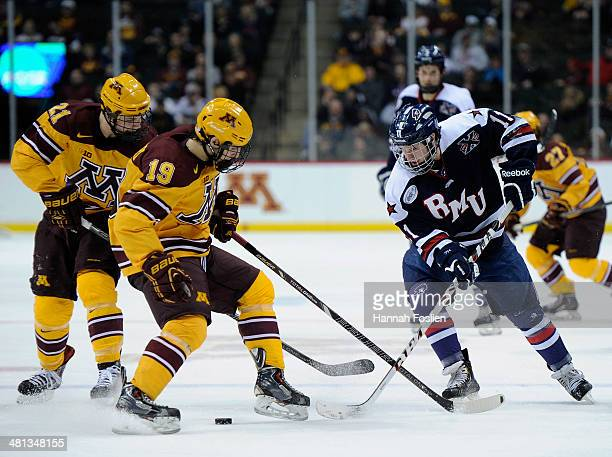 Vinni Lettieri of the Minnesota Golden Gophers gets the puck away from Jeff Jones of the Robert Morris Colonials during the second period of the West...