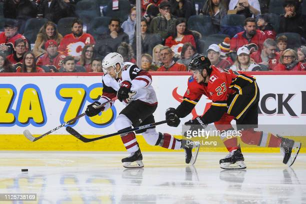 Vinnie Hinostroza of the Arizona Coyotes chases the puck against Sean Monahan of the Calgary Flames during an NHL game at Scotiabank Saddledome on...