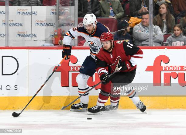 Vinnie Hinostroza of the Arizona Coyotes skates with the puck past Leon Draisaitl of the Edmonton Oilers during the third period at Gila River Arena...