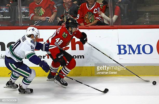 Vinnie Hinostroza of the Chicago Blackhawks advances the puck under pressure from Markus Granlund of the Vancouver Canucks at the United Center on...