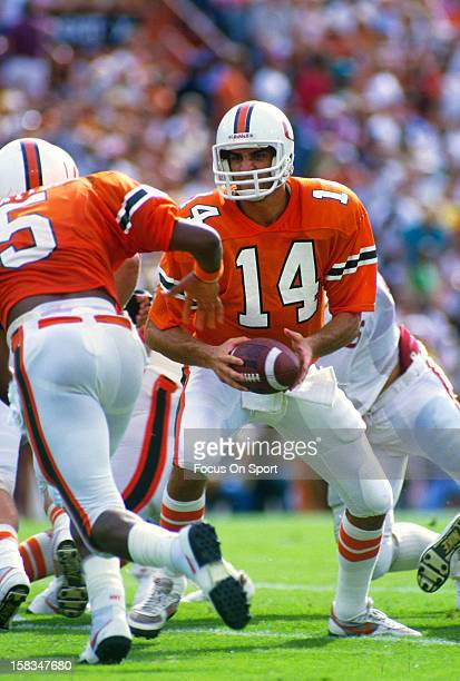 Vinny Testaverde of the Miami Hurricanes turns to hand the ball off to Alonzo Highsmith against the Florida State Seminoles during an NCAA football...
