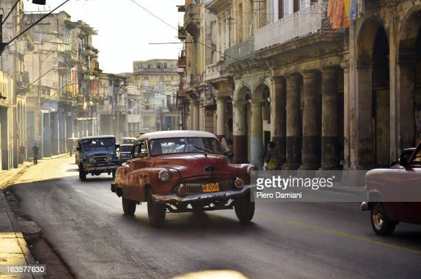 CONTENT] Vintage 1950s american style cars in Havana surrounded by decaying colonial style residential buildings