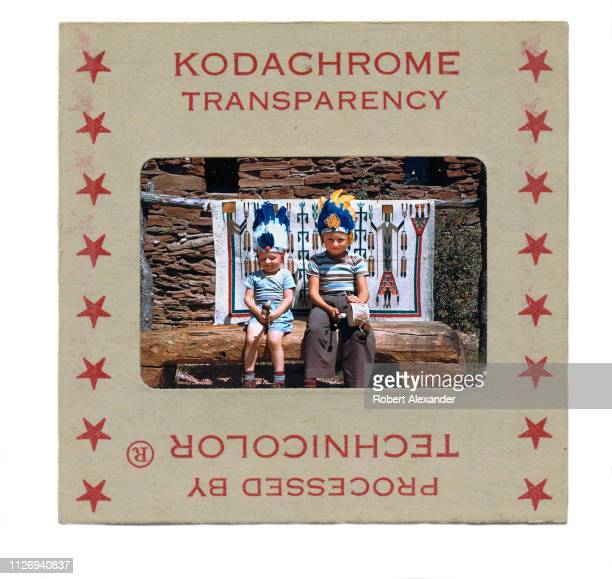 A vintage 1950s Kodachrome transparency in a cardboard mount The photographic slide of two boys sitting in front of a Navajo blanket was taken...