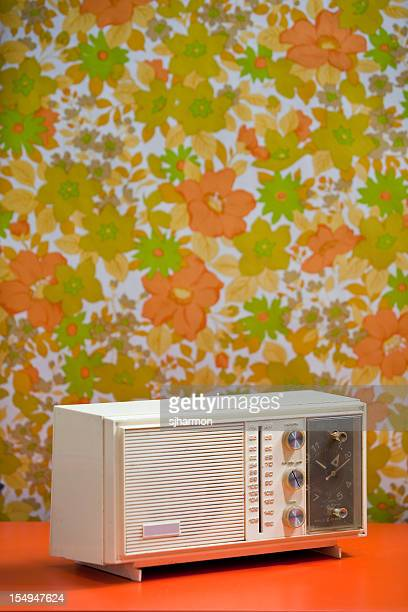 Vintage 60's 70's Clock Radio with floral wallpaper background orange