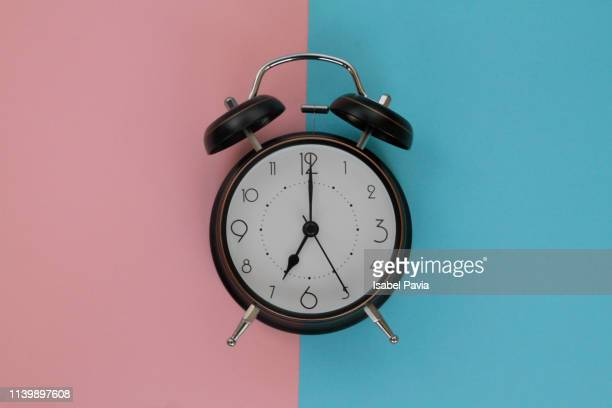vintage alarm clock on pink and blue background - countdown clock stock-fotos und bilder