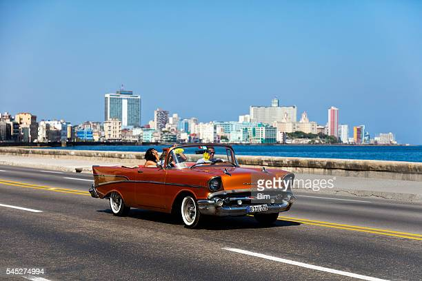 Vintage American car with tourists on Malecon, Havana, Cuba