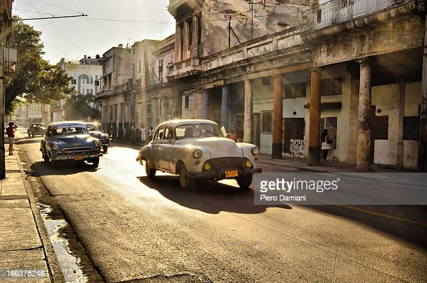 Vintage American cars driving through Havana streets surrounded by beautiful colonial style buildings