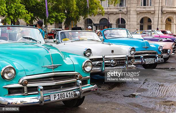 Vintage American cars parked in a line up formation Green white blue purple