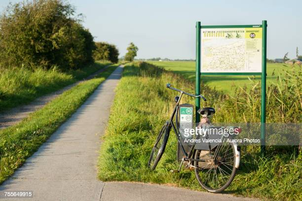 Vintage and black bike standing by junction indicator with map, Groningen, Netherlands