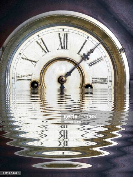 Vintage antique grandfather clock face with Roman numeral numbers and hour and second hands reflected in rippled water distortion.