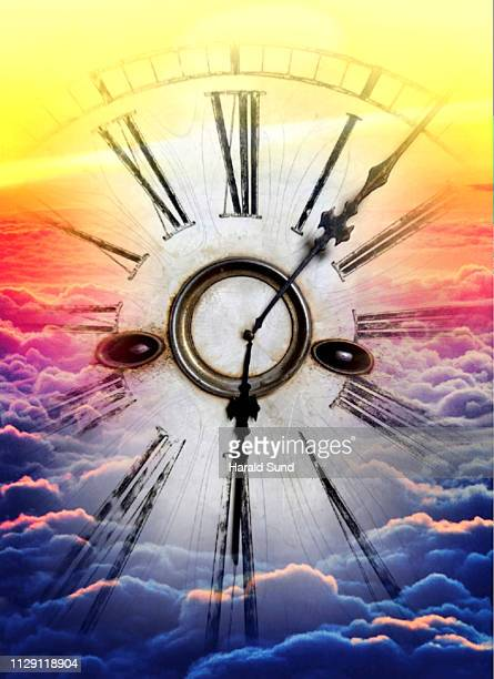 Vintage antique grandfather clock face with Roman numeral numbers and hour and second hands floating in a sea of sun lit clouds.