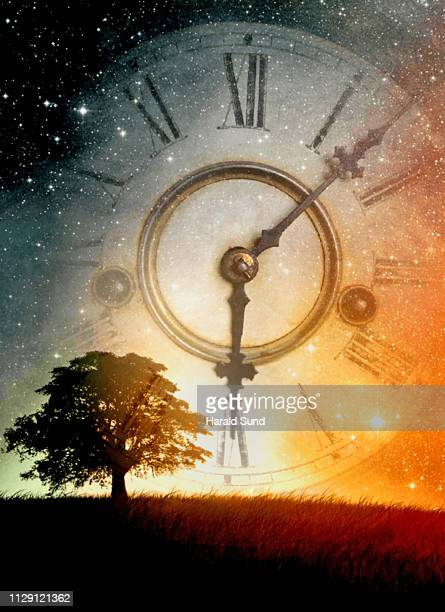 Vintage antique grandfather clock face with Roman numeral numbers and hour and second hands with a silhouette tree on a horizon line and a celestial sky filled with stars.