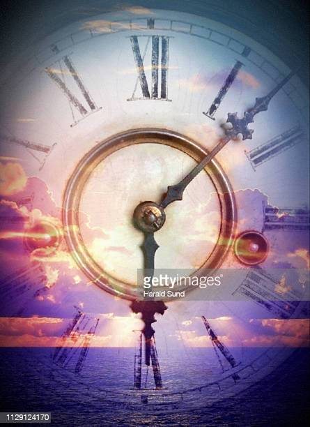 Vintage antique grandfather clock face with Roman numeral numbers and hour and second hands with an ocean and sea of sun lit clouds.