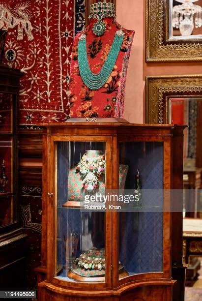 Vintage armoire displaying jewelry amidst art and artefacts, velvet jewelry busts and mirrors at Sabyasachi Jewelry, Indian couturier and jewelry...