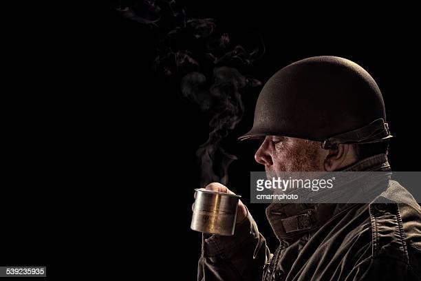 vintage army soldier bebiendo café caliente en una lata de fútbol - soldado ejército de tierra fotografías e imágenes de stock