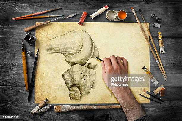 vintage artist's equipment on desk and drawing hand