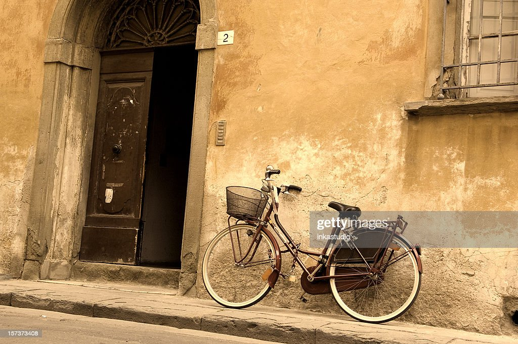 A vintage bicycle leaning against an old building : Stock Photo