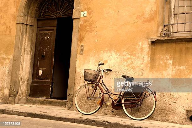 A vintage bicycle leaning against an old building