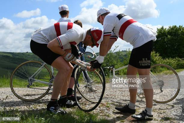 Vintage bicycle's enthusiasts fix a puncture during a ride on the white roads of Tuscany during the Eroica Montalcino festive event on May 7 2017...
