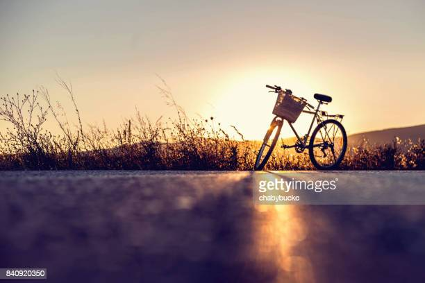 Bicicleta Vintage estacionado en la carretera al atardecer. Copia espacio.