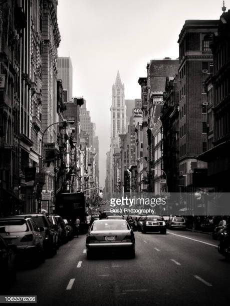 Vintage black and white image of a car driving along Broadway, framed by high-rise buildings. The famous Woolworth Building skyscraper is in the background.