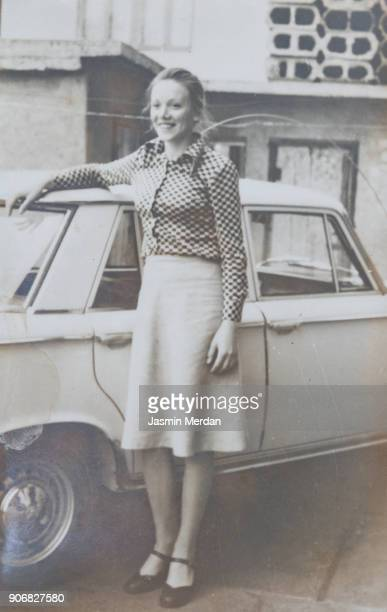 vintage black and white photo of woman standing next to car - archiefbeelden stockfoto's en -beelden