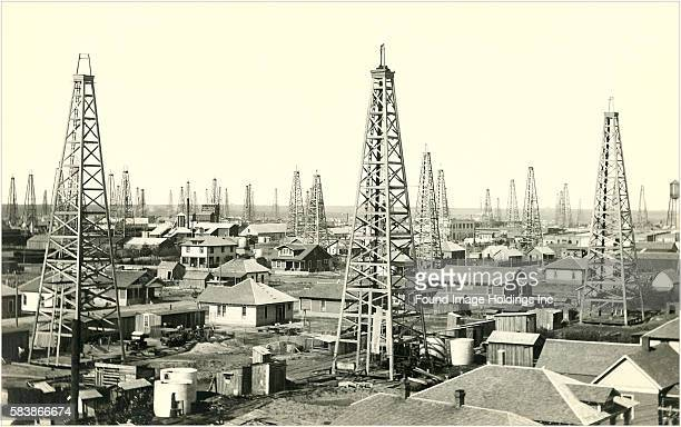 Vintage black and white photograph of a newly constructed oil boom town with oil well towers and new housing stretching toward the horizon 1910s
