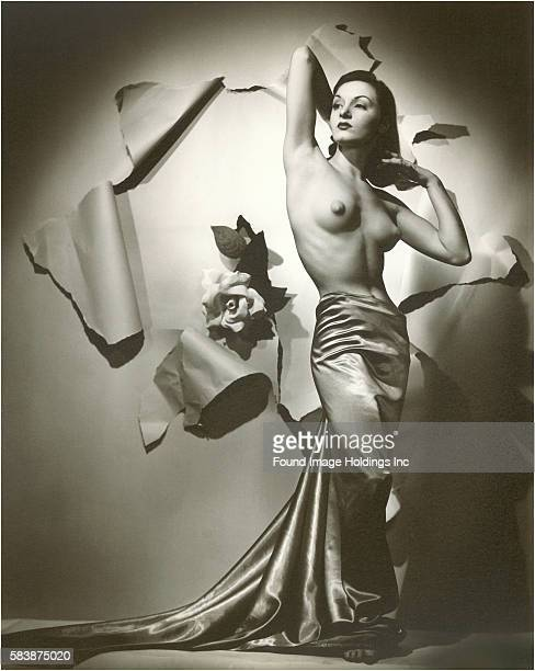 Vintage black and white photograph of a topless woman with satin wrapped around her lower body posing in front of a large rose and torn wallpaper in...