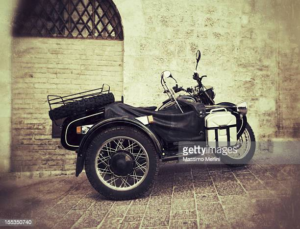 Vintage black sidecar outdoors against brick wall.