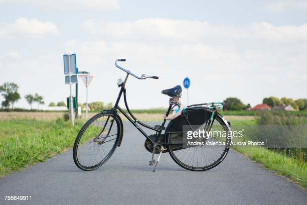 vintage black typically dutch bicycle with worn leather seat is propping up on bike path, groningen, netherlands  - groningen province stock photos and pictures