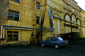 vintage blue car near old factory