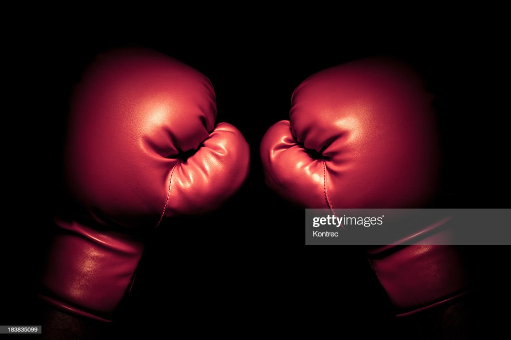 Vintage boxing gloves emerging from black background : Stock Photo