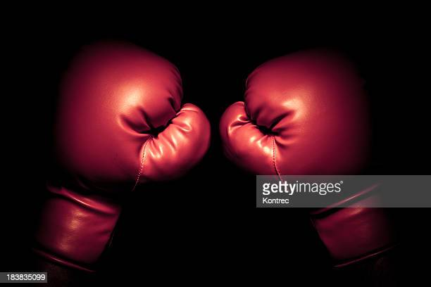 vintage boxing gloves emerging from black background - boxing gloves stock photos and pictures