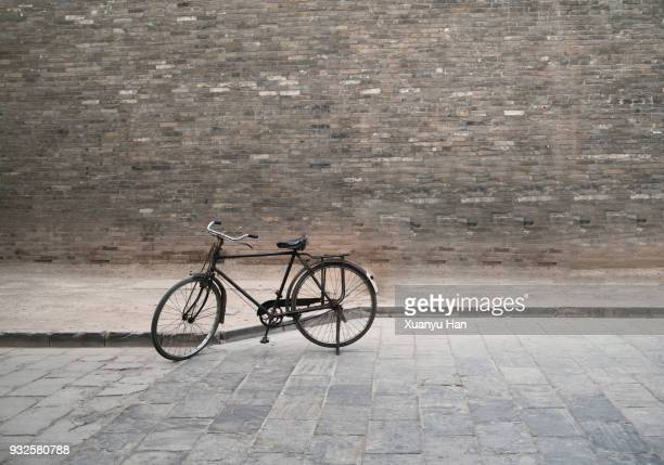 vintage bycicle and brick wall - black alley stock photos and pictures