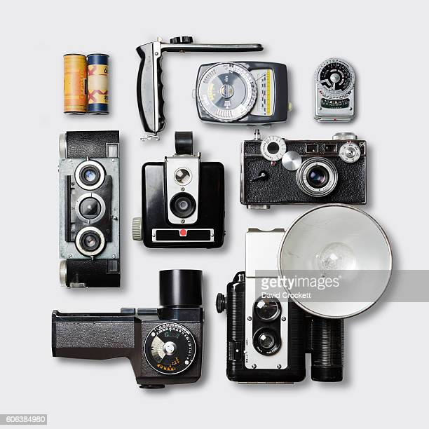 Vintage cameras and photography equipment on white tabletop, high angle view.