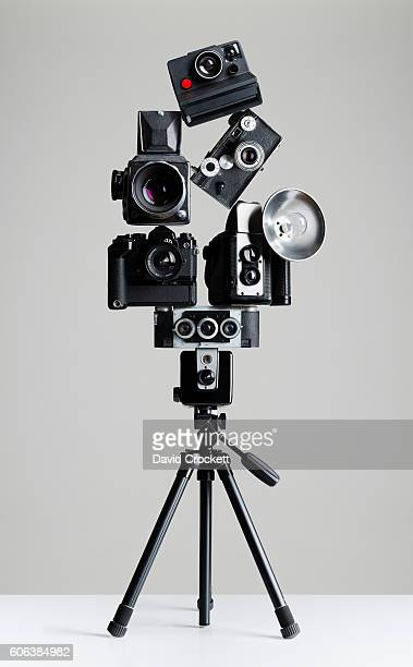 vintage cameras balanced on tripod - photographic film camera stock photos and pictures