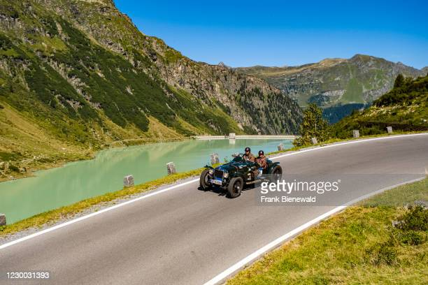 Vintage car Alvis Firebird Special driving past a lake on Silvretta Hochalpenstrasse during the Arlberg Classic Car Rally.