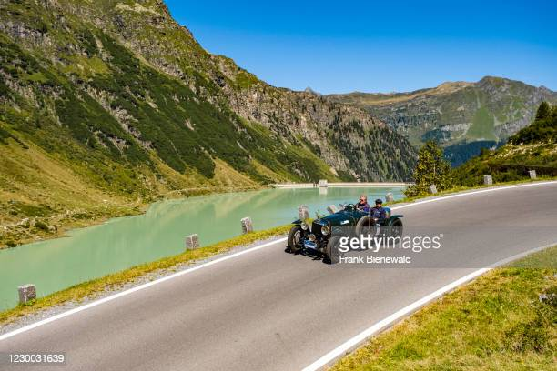Vintage car Alvis Speed 20 Special driving past a lake on Silvretta Hochalpenstrasse during the Arlberg Classic Car Rally.