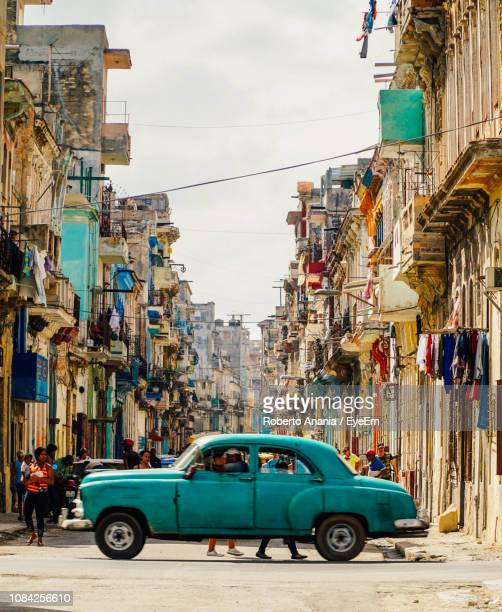 vintage car amidst buildings - cuba foto e immagini stock