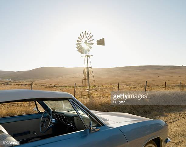 Vintage Car and Windmill Near Agricultural Fields