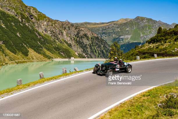 Vintage car Aston Martin Mk II Ulster Special driving past a lake on Silvretta Hochalpenstrasse during the Arlberg Classic Car Rally.