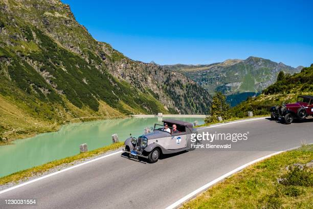 Vintage car Bentley 3 1/2 L driving past a lake on Silvretta Hochalpenstrasse during the Arlberg Classic Car Rally.
