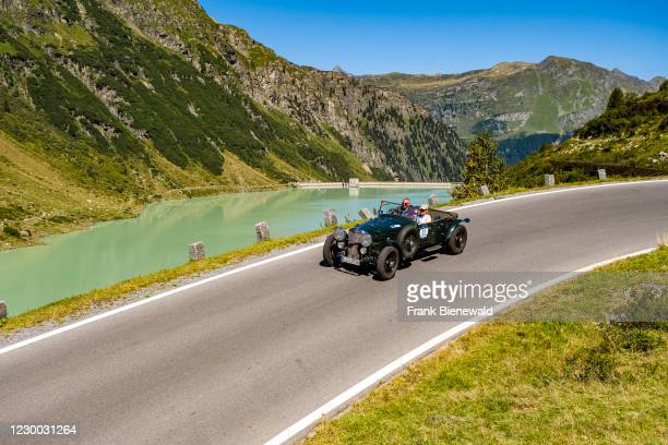 Vintage car Bentley 3 1/2 Litre Van Den Plas driving past a lake on Silvretta Hochalpenstrasse during the Arlberg Classic Car Rally.