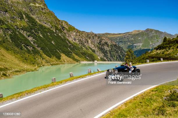 Vintage car Bentley 3.5 SS Spezial Eddy Hall Open driving past a lake on Silvretta Hochalpenstrasse during the Arlberg Classic Car Rally.