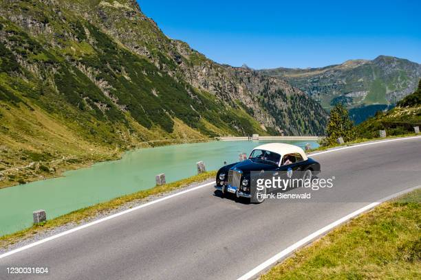 Vintage car Bentley Mk VI Graber Coupe driving past a lake on Silvretta Hochalpenstrasse during the Arlberg Classic Car Rally.