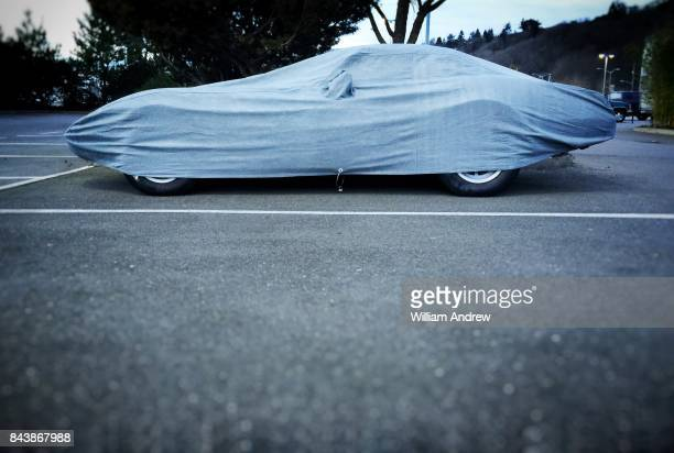Vintage car covered with cloth cover in parking lot