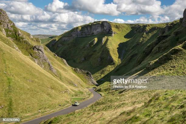 vintage car driving through winnats pass, peak district, derbyshire - mountain pass stock pictures, royalty-free photos & images