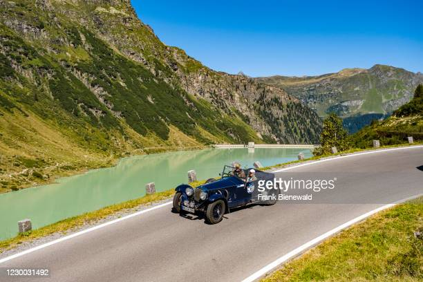 Vintage car Invicta Tourer S-Type driving past a lake on Silvretta Hochalpenstrasse during the Arlberg Classic Car Rally.