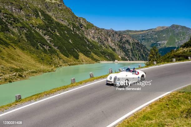Vintage car Jaguar XK 120 OTS SE Roadster driving past a lake on Silvretta Hochalpenstrasse during the Arlberg Classic Car Rally.
