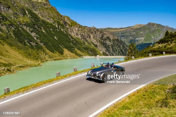 Vintage car Jaguar XK 150 Cabrio driving past a lake on Silvretta Hochalpenstrasse during the Arlberg Classic Car Rally.